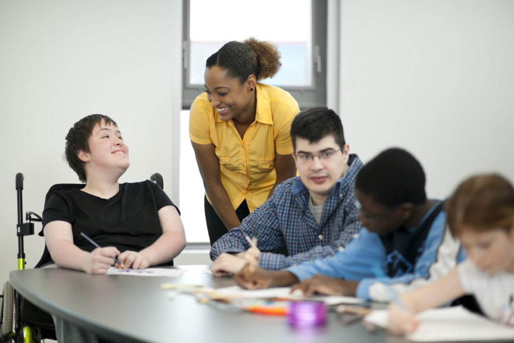 A diverse group of students with disabilities sit at a table and work on arts and crafts